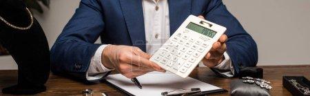 Photo pour Vue recadrée de l'évaluateur de bijoux montrant la calculatrice près du presse-papiers et des bijoux sur la table, vue panoramique - image libre de droit