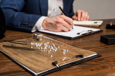 """Photo pour Point de mire sélectif de pierres précieuses et d'outils près de l """"évaluateur de bijoux écriture sur planche à reliure sur table isolée sur gris - image libre de droit"""