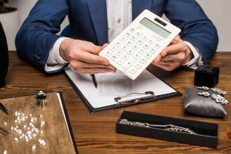 Photo pour Vue recadrée de l'évaluateur de bijoux tenant la calculatrice près du presse-papiers et des bijoux avec des pierres précieuses sur la table - image libre de droit