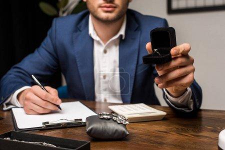 Photo pour Vue agrandie d'un évaluateur de bijoux tenant une boîte avec une bague et écrivant sur une planche à reliure près de bijoux sur une table en bois - image libre de droit