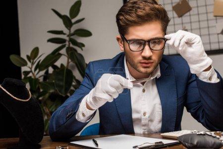 Photo pour Évaluateur de bijoux en lunettes Examen de pierres précieuses Près d'une calculatrice et d'un planche à pince sur une table dans un atelier - image libre de droit