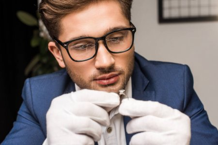 Photo pour Concentration sélective du bel évaluateur de bijoux en gants tenant la bague avec la pierre précieuse dans l'atelier - image libre de droit