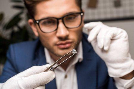 Photo pour Concentration sélective de l'évaluateur de bijoux tenant la pierre précieuse dans une pince à épiler tout en travaillant en atelier - image libre de droit