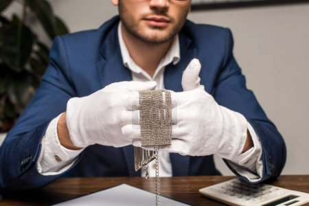 """Photo pour Vue agrandie de l """"évaluateur de bijoux en gants tenant un collier près d'une calculatrice et d'une planche à pince sur une table dans un atelier - image libre de droit"""