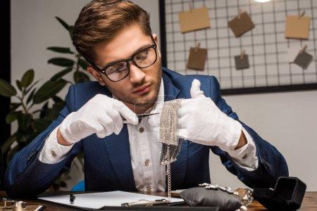 Photo pour Évaluateur de bijoux tenant une pince à épiler et un collier près du presse-papiers et des bijoux sur la table - image libre de droit