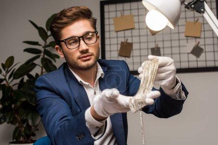 Photo pour Concentration sélective de l'évaluateur de bijoux tenant collier près de la lampe dans l'atelier - image libre de droit