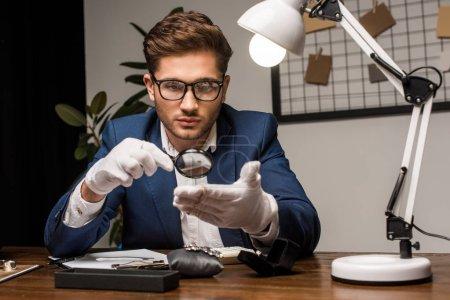 Photo pour Bijoux évaluateur examen bracelet avec loupe près de bijoux sur la table - image libre de droit