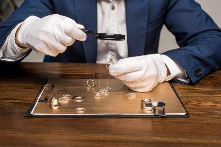 Photo pour Vue recadrée de l'évaluateur de bijoux avec loupe examinant bague de bijoux près de bord sur la table sur fond gris - image libre de droit