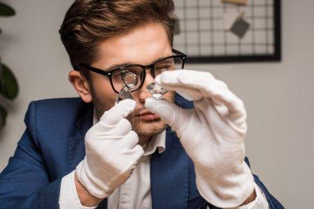 Photo pour Évaluateur de bijoux avec loupe examinant la pierre précieuse en atelier - image libre de droit