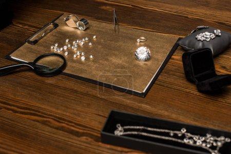Photo pour Concentration sélective de pierres précieuses, bijoux et loupes avec pince à épiler à bord sur table en bois - image libre de droit