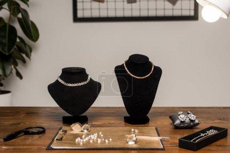 Photo pour Colliers de bijoux sur colliers près de pierres précieuses et loupes à bord sur table en atelier - image libre de droit