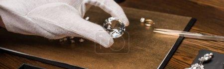 Photo pour Vue agrandie d'un évaluateur de bijoux tenant des pierres précieuses près de bijoux à bord sur une table en bois, photo panoramique - image libre de droit