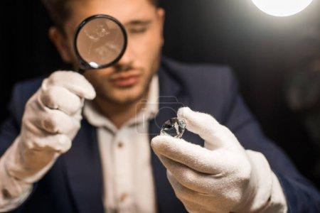 Photo pour Concentration sélective de l'évaluateur de bijoux examinant la pierre précieuse avec loupe sur fond noir - image libre de droit