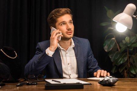 Photo pour Pensive évaluateur de bijoux parler sur smartphone et en utilisant la calculatrice près de bijoux sur la table dans l'atelier - image libre de droit