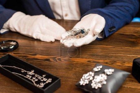 Photo pour Vue agrandie d'un évaluateur de bijoux tenant des bijoux près d'une loupe sur une table sur fond noir - image libre de droit