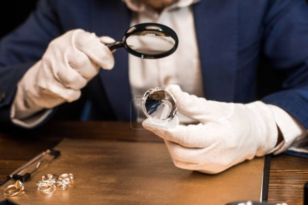 Photo pour Cropped view of jewelry appraiser holding gemstone and magnifying glass near jewelry rings on board on table isolated on black - image libre de droit