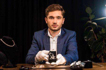 Photo pour Évaluateur de bijoux regardant la caméra et tenant collier près de bijoux sur la table dans l'atelier - image libre de droit