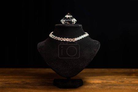 Photo pour Collier stand avec collier et diamant sur table en bois isolé sur noir - image libre de droit