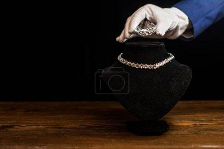 Photo pour Vue recadrée de l'évaluateur de bijoux tenant le diamant près du collier sur le support de collier sur la table en bois isolé sur noir - image libre de droit