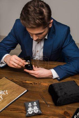 Photo pour Évaluateur de bijoux examinant bague de bijoux avec loupe près de bijoux sur la table dans l'atelier - image libre de droit