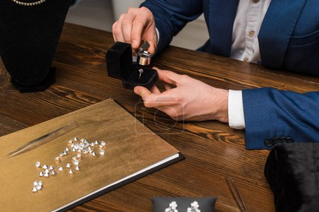 Photo pour Cropped view of jewelry appraiser examining jewelry ring with magnifying glass near gemstones on wooden table - image libre de droit