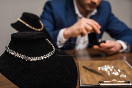 Photo pour Mise au point sélective des colliers sur les colliers et évaluation des bijoux à table isolés sur gris - image libre de droit