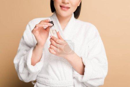 Photo pour Vue recadrée de sourire belle femme asiatique en peignoir tenant compte compte compte-gouttes et bouteille avec sérum sur fond beige - image libre de droit