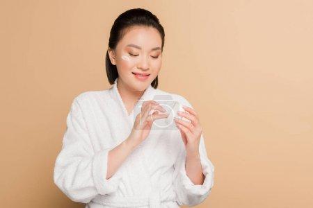 Photo pour Belle femme asiatique souriante en peignoir avec de la crème pour le visage sur fond beige - image libre de droit