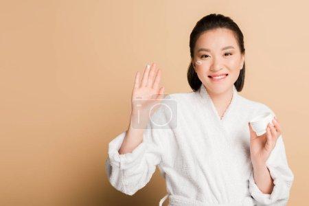 Photo pour Belle femme asiatique souriante en peignoir avec crème pour le visage sur la joue et doigt sur fond beige - image libre de droit