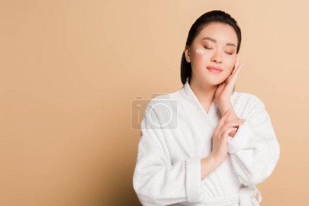 Photo pour Heureux belle asiatique femme en peignoir avec visage crème sur la joue et les yeux fermés sur fond beige - image libre de droit