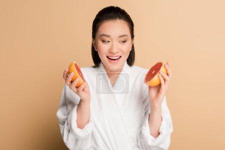Photo pour Heureux belle asiatique femme en peignoir avec pamplemousse moitiés sur beige fond - image libre de droit