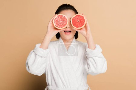 Photo pour Choqué belle asiatique femme en peignoir avec pamplemousse moitiés sur les yeux sur fond beige - image libre de droit