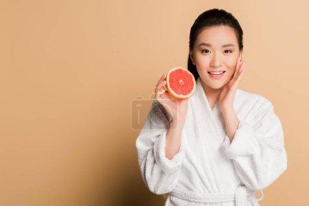 Photo pour Heureux belle asiatique femme en peignoir avec pamplemousse moitié sur beige fond - image libre de droit
