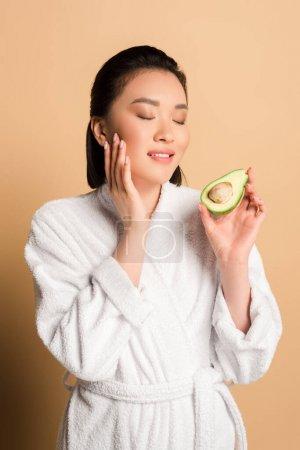 Photo pour Belle femme asiatique en peignoir avec avocat moitié toucher le visage sur fond beige - image libre de droit