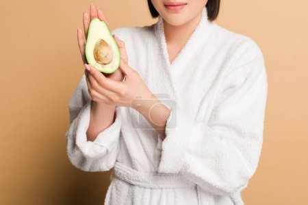 Photo for Cropped view of happy beautiful asian woman in bathrobe with avocado half on beige background - Royalty Free Image