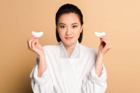 Photo pour Sourire belle asiatique femme en peignoir tenant oeil patchs sur fond beige - image libre de droit