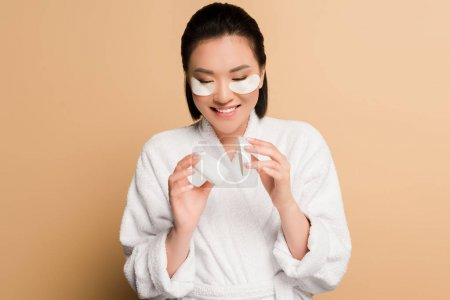 Photo pour Heureux belle asiatique femme en peignoir avec oeil patches sur visage tenant conteneur sur fond beige - image libre de droit