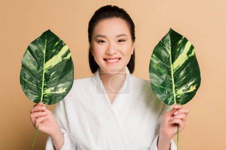 Photo pour Heureux belle asiatique femme en peignoir avec vert feuilles sur beige - image libre de droit