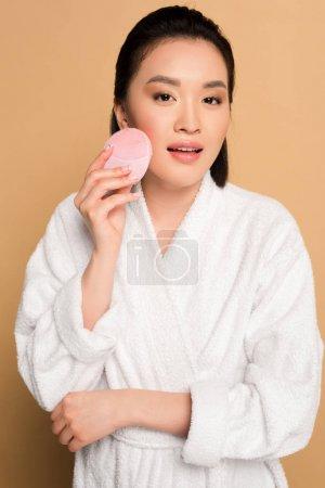 Photo pour Belle asiatique femme en peignoir en utilisant visage nettoyage brosse sur beige fond - image libre de droit