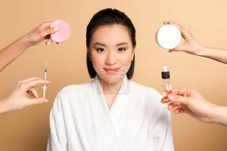Photo pour Sourire belle asiatique femme en peignoir près des mains avec brosse de nettoyage du visage, seringue, crème cosmétique et huile sur fond beige - image libre de droit