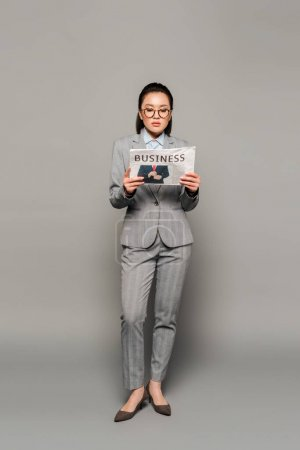 Photo for Young businesswoman in eyeglasses reading business newspaper on grey background - Royalty Free Image