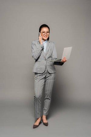 Photo pour Jeune femme d'affaires souriante dans des lunettes à l'aide d'un ordinateur portable et parler sur smartphone sur fond gris - image libre de droit