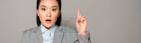 Photo pour Excitée jeune femme d'affaires en costume montrant geste idée isolé sur fond gris, vue panoramique - image libre de droit