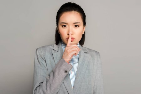 Photo for Young businesswoman in suit showing shh gesture on grey background - Royalty Free Image
