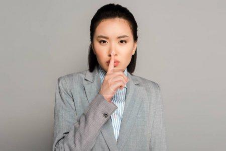 Photo pour Young businesswoman in suit showing shh gesture on grey background - image libre de droit