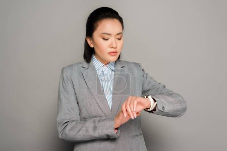 Photo for Young businesswoman in suit looking at wristwatch on grey background - Royalty Free Image