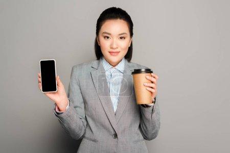 Foto de Feliz joven empresaria con taza de papel sosteniendo teléfono inteligente sobre fondo gris - Imagen libre de derechos