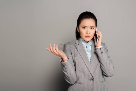 Photo pour Confused young businesswoman in suit talking on smartphone on grey background - image libre de droit