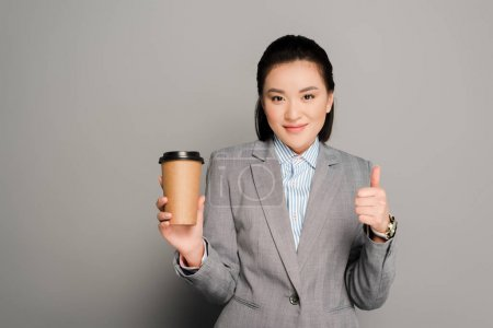Photo pour Happy young businesswoman with paper cup showing thumb up on grey background - image libre de droit
