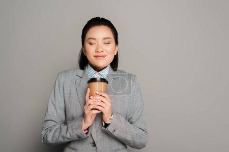Photo pour Une jeune femme d'affaires heureuse avec une tasse de papier et les yeux fermés sur fond gris - image libre de droit